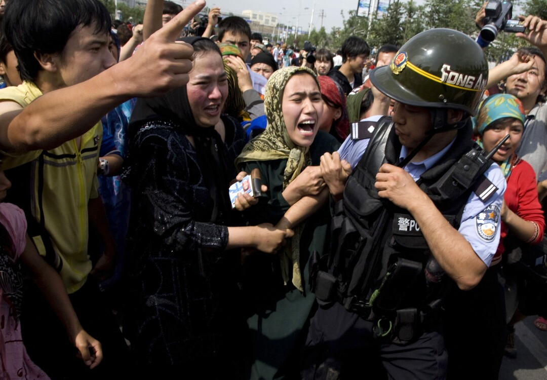 Uighur women grab a police officer as they protest in Urumqi, Xinjiang.