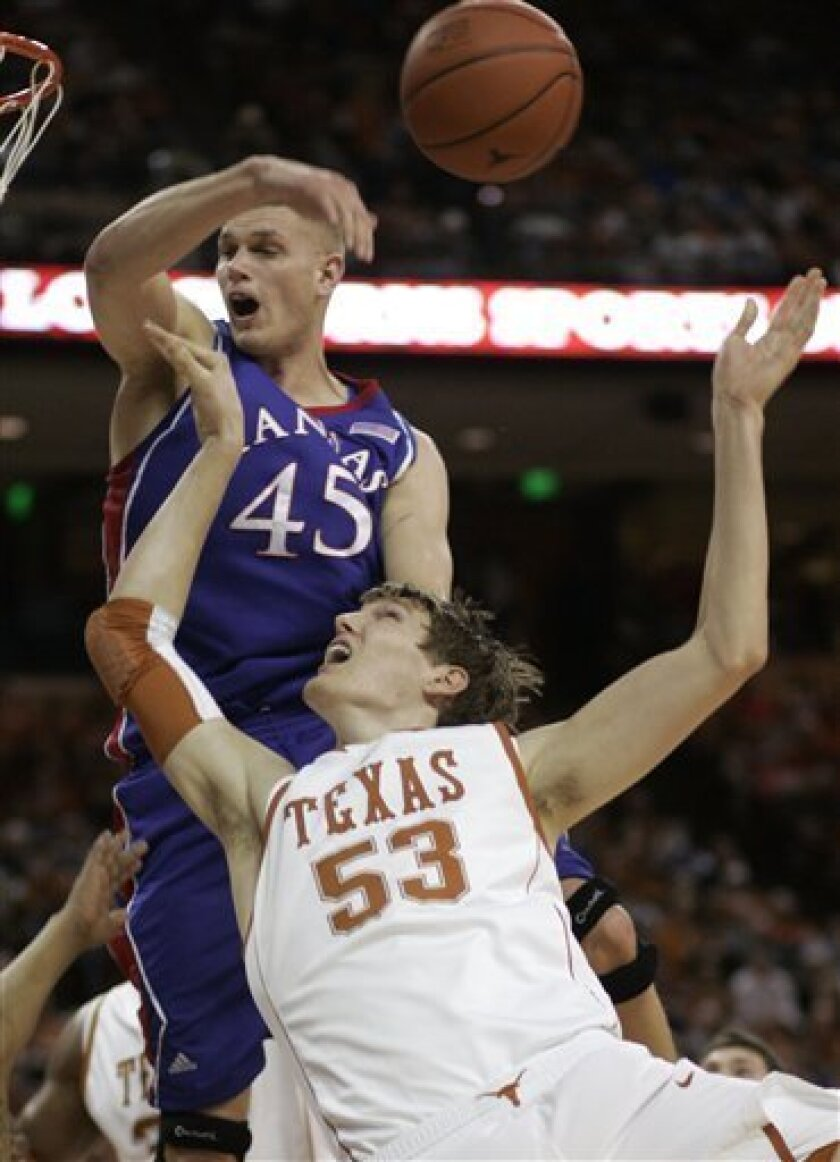 Kansas center Cole Aldrich (45) rejects a shot attempt by Texas center Clint Champman (53) during the first half of an NCAA college basketball game Monday, Feb. 8, 2010, in Austin, Texas. (AP Photo/Harry Cabluck)