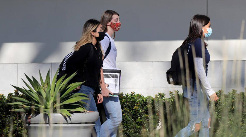 Students wear facial masks on the 1100 block of Irvine Avenue, in Newport Beach in November 2020.