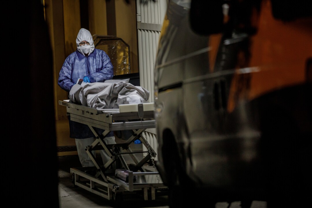 A medical worker at Tijuana General Hospital checks paperwork before handing off a corpse for transfer to the morgue.