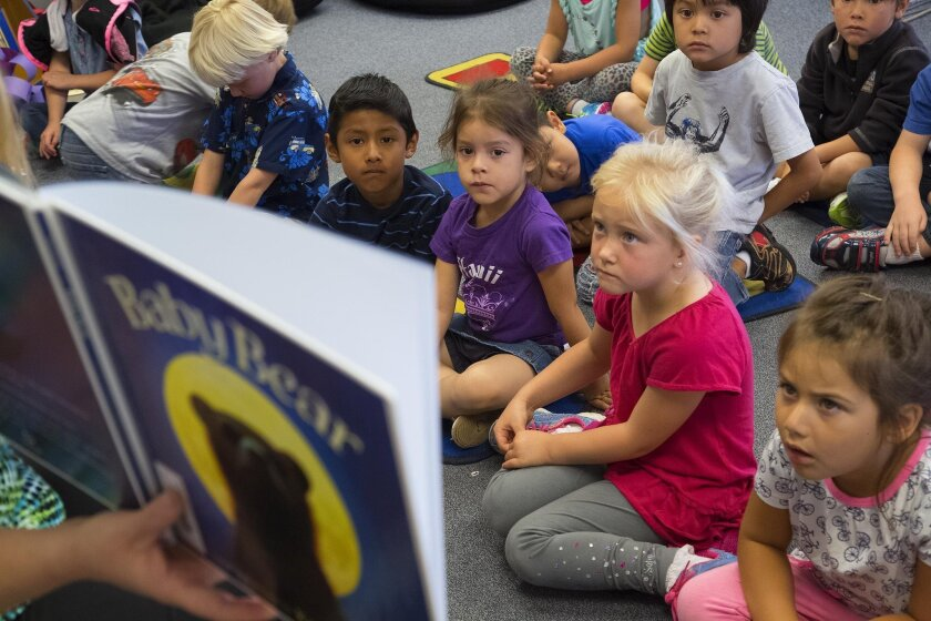 At Jefferson Elementary School in Carlsbad, young children in Laurel Ferreiras' transitional kindergarten class listen to story read from book during their time in classroom.