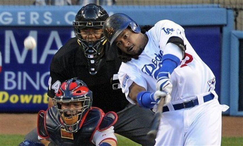 Los Angeles Dodgers Manny Ramirez hits a two-run home run as St. Louis Cardinals catcher Yadier Molina and home plate umpire Kerwin Danley look on during the first inning of a baseball game Wednesday, June 9, 2010, in Los Angeles. (AP Photo/Mark J. Terrill)