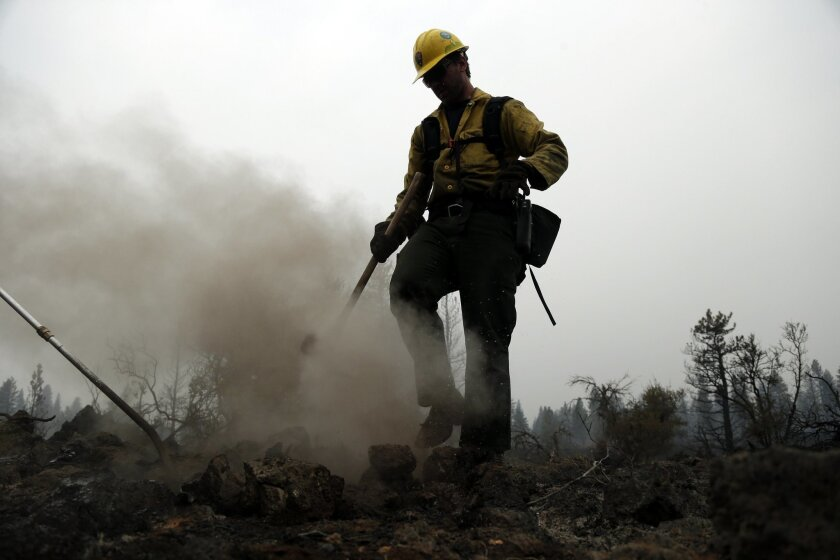 Remington Jones, of the Point Reyes National Seashore, Calif., Engine 1130 looks for hot spots left behind by the Eiler Fire on Tuesday, Aug. 5, 2014, near Burney, Calif. The fire is threatening more than 700 homes, some of which have been evacuated. (AP Photo/Marcio Jose Sanchez)