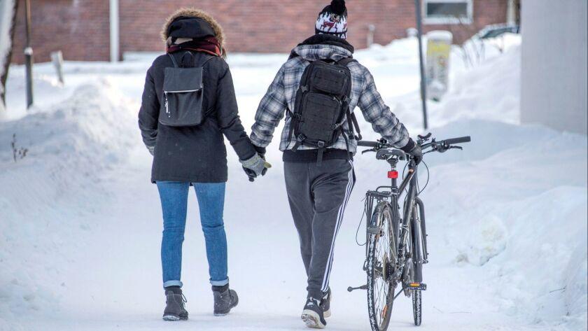 A couple walks on a snow-covered street in Jyvaskyla, Finland, on Jan. 18.