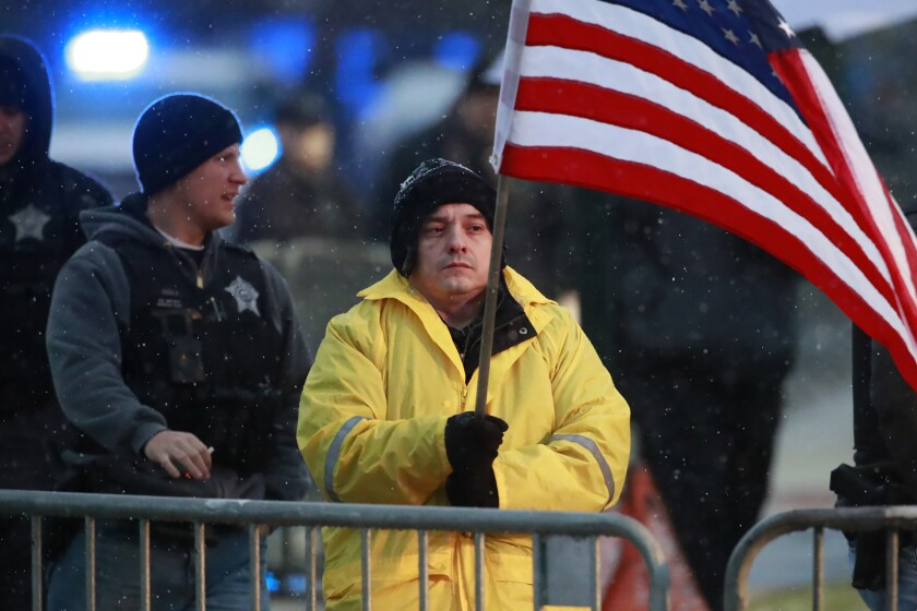 FILE - In this Nov. 25, 2018 file photo, State Rep. Jaime Andrade holds a flag outside the visitation for Chicago police Officer Samuel Jimenez at a funeral home in Des Plaines, Ill.A federal bribery charge against an Illinois legislator has led to questions about whether lawmakers be allowed to lobby other units of government. Illinois like most states allows legislators to lobby outside state government. Andrade said he registered as a Chicago lobbyist and started charging for his services when the state budget crisis from 2015 to 2017 forced lawmakers to go without paychecks.