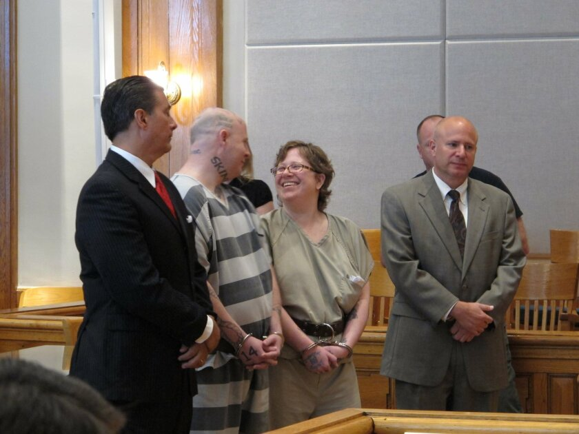 Jeremy Moody, left, talks to his wife, Christine Moody, right, while standing with their lawyers shortly before they were both sentenced to life in prison on Tuesday, May 6, 2014, in Union, S.C. Prosecutors said the couple killed Charles Parker in his home in July 2013 because he was a sex offender