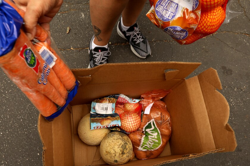 Yanira C. Ruiz, 50, looks over her box of produce she received at a food giveaway.