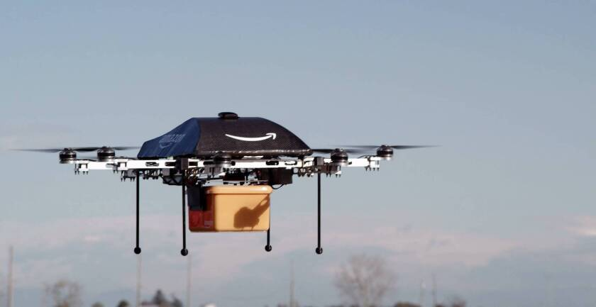 An unmanned aerial vehicle carries a package from Amazon.
