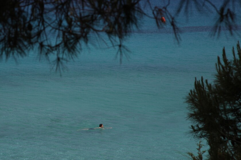 Sunday, May 10, 2020 photo, a lone swimmer wades through the clear waters of 'Konnos' beach in Ayia Napa, a seaside resort that's popular with tourists from Europe and beyond. Cyprus' beleaguered tourism sector got some good news after the government announced on Friday, July 3, 2020, that travelers from the U.K. will be allowed entry into the east Mediterranean island nation next month without having to undergo a compulsory 14-day quarantine. (AP Photo/Petros Karadjias)