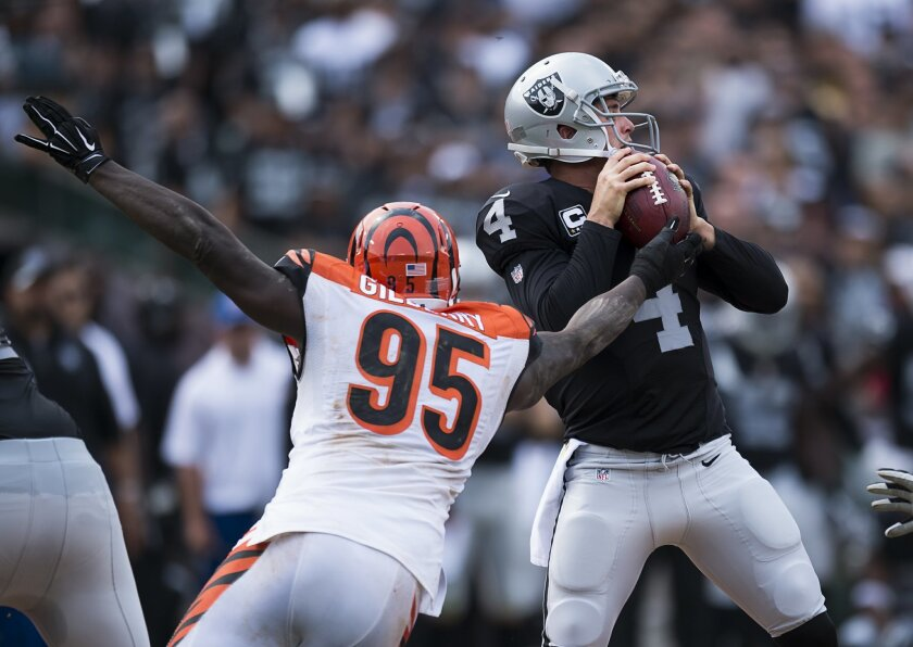Oakland Raiders quarterback Derek Carr (4) throws an incomplete pass after being pressured by Cincinnati Bengals defensive end Wallace Gilberry (95) during an NFL football game in Oakland, Calif., Sunday, Sept. 13, 2015. (Paul Kitagaki Jr./The Sacramento Bee via AP) MAGS OUT; TV OUT (KCRA3, KXTV10, KOVR13, KUVS19, KMAZ31, KTXL40) MANDATORY CREDIT