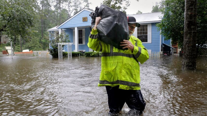 Mike Battles, brother in law of homeowner Doug Glassel, wades through flood waters as he carries food from Glassel's flooded two-story home in Spring, Texas on Aug. 29.