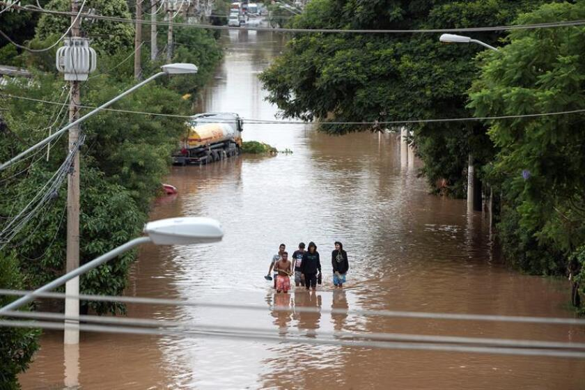 People walk through the affected streets of Sao Paulo, Brazil, on March 11, 2019, after heavy rains had caused mudslides and floods on the metropolis. EPA-EFE/Sebastiao Moreira