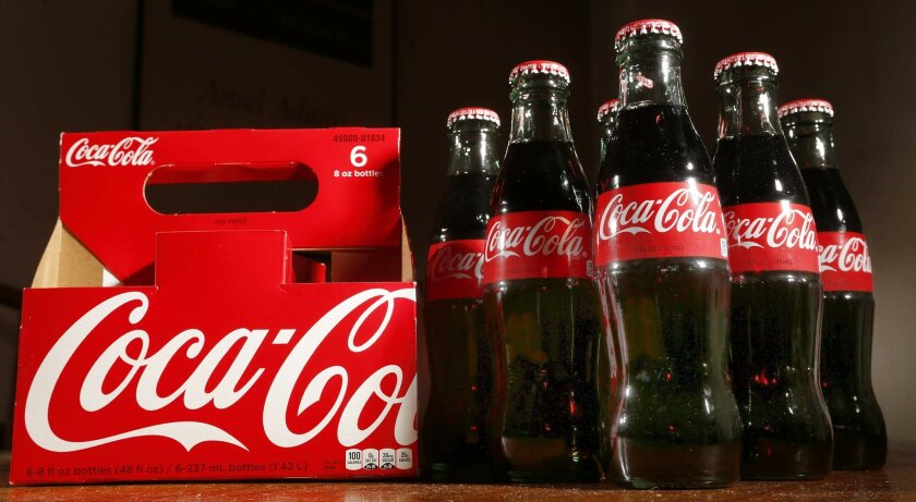 This Thursday, April 28, 2016, photo shows bottles of Coca-Cola in Concord, N.H. Coca-Cola reports financial results Wednesday, July 27, 2016. (AP Photo/Jim Cole)