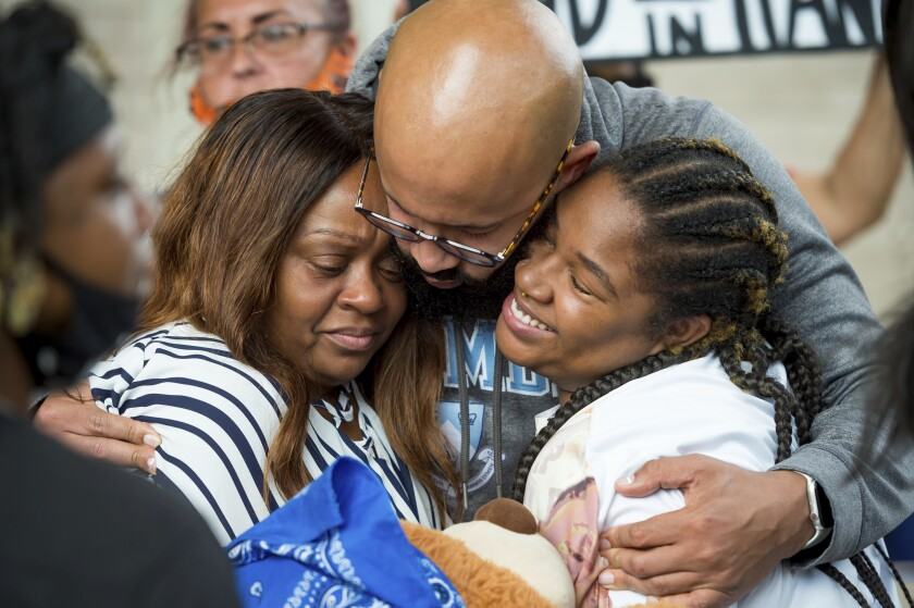 FILE - In this Tuesday, May 11, 2021 file photo, Michelle Pellerin, Trayford Pellerin's mother at left, is comforted by family and friends during a news conference at Lafayette Parish Courthouse in Lafayette, La. State police have released a report saying officers in a south Louisiana city police department were justified in last year's fatal shooting of a Black man. The 152-page report was written in December but released Wednesday, July 14, 2021. It comes two months after a Lafayette Parish grand jury declined to indict Lafayette Police Department officers in the August shooting of Trayford Pellerin. (Scott Clause/The Daily Advertiser via AP, File)