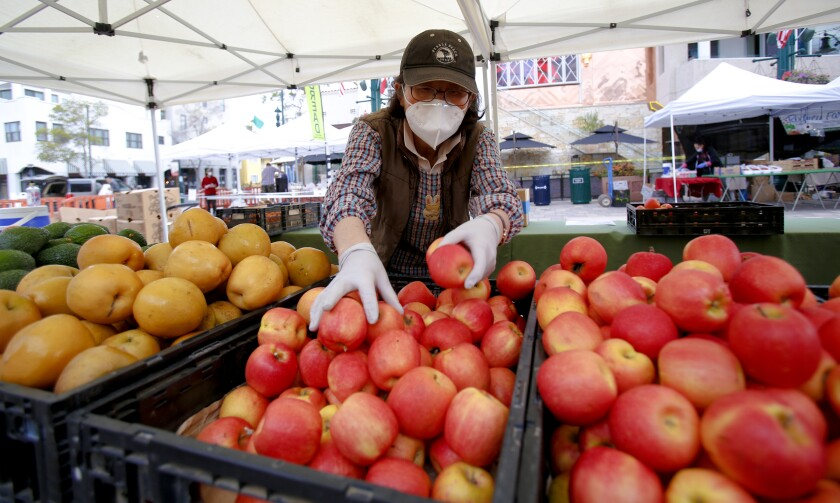 In this file photo, Kyung Jun with Jacy Farm stocked fresh fruits for her customers at the Farmers Market in Little Italy. Employees at grocery stores are required to wear a cloth mask covering their face, and a new order will require food servers, child-care providers and people who work in banks and public transportation to also cover the faces beginning Monday.