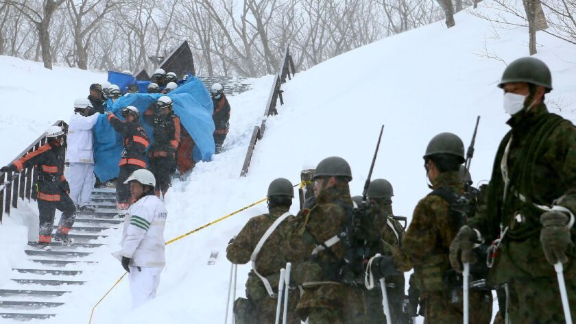 Firefighters carry a survivor they rescued from the site of an avalanche in Nasu town, Tochigi prefe