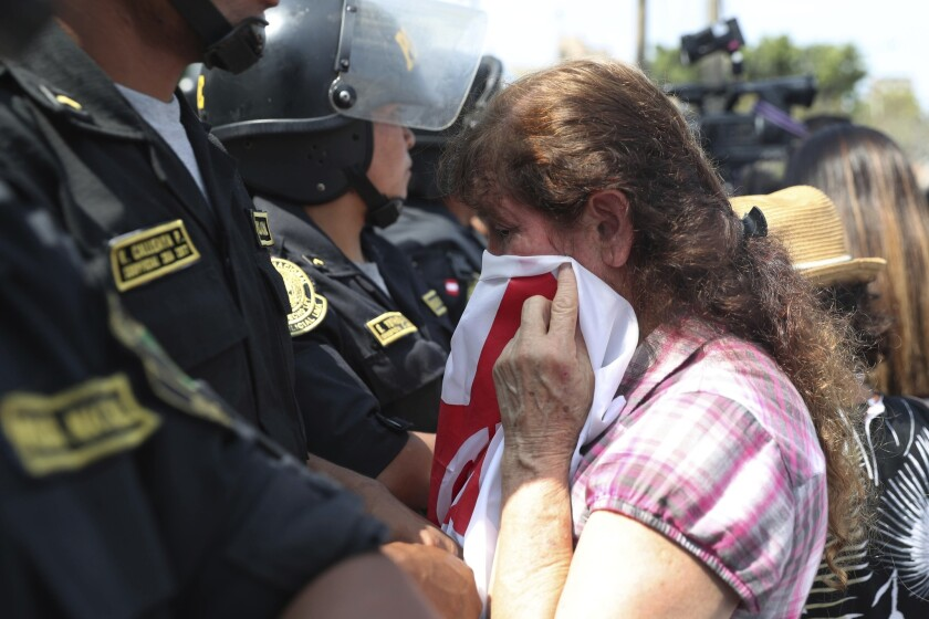 A supporter of former Peruvian President Alan Garcia cries as she learns of his death outside the Lima hospital where he was treated.