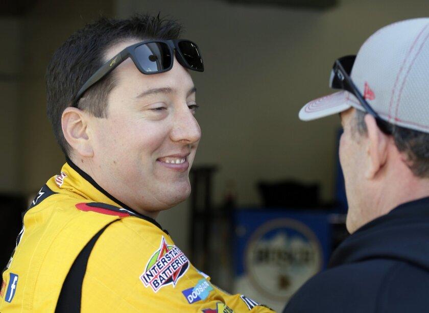 Kyle Busch, left, talks to a crew member during practice for Sunday's NASCAR Daytona 500 Sprint Cup series auto race at Daytona International Speedway in Daytona Beach, Fla., Friday, Feb. 19, 2016. (AP Photo/Terry Renna)