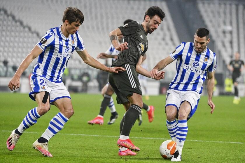 Bruno Fernandes (centro) del Manchester United pugna un balón con Robin Le Normand