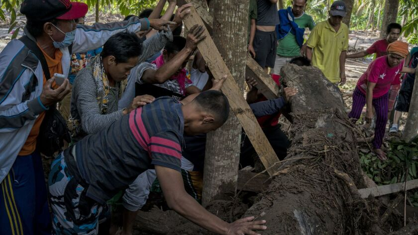 Family and friends recover the body of Amir Ampaso, 60, who was killed in Typhoon Tembin on Christmas Day in the Philippines.