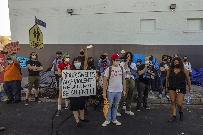 Masked protesters surround sidewalk tents to stop city workers from removing them during a cleanup in Hollywood