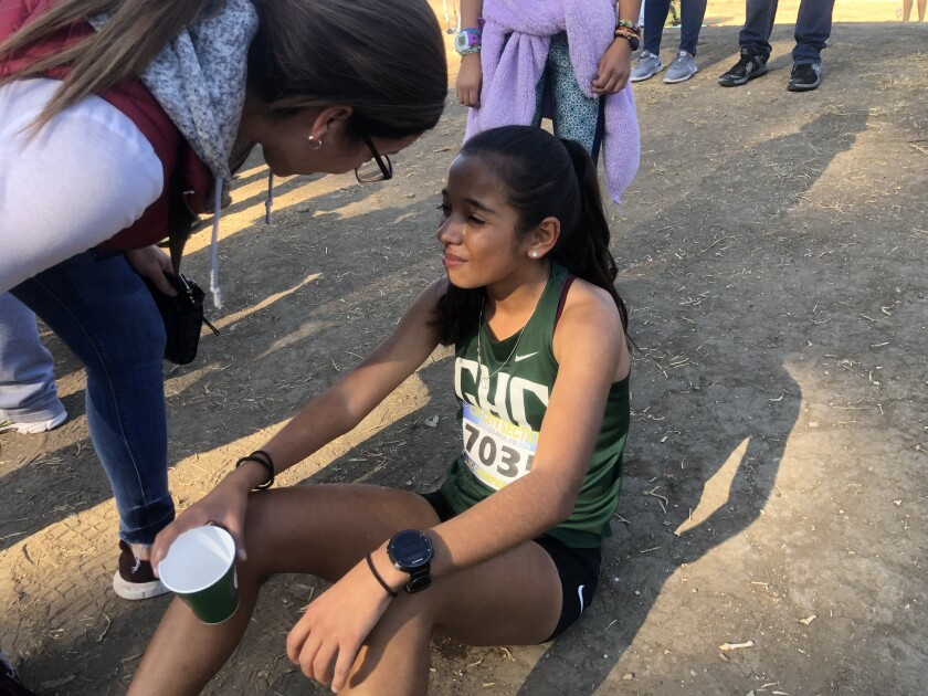 Sophomore Sofia Abrego of Granada Hills receives support from a family friend after winning her second consecutive City Section Division I girls' cross-country championship.