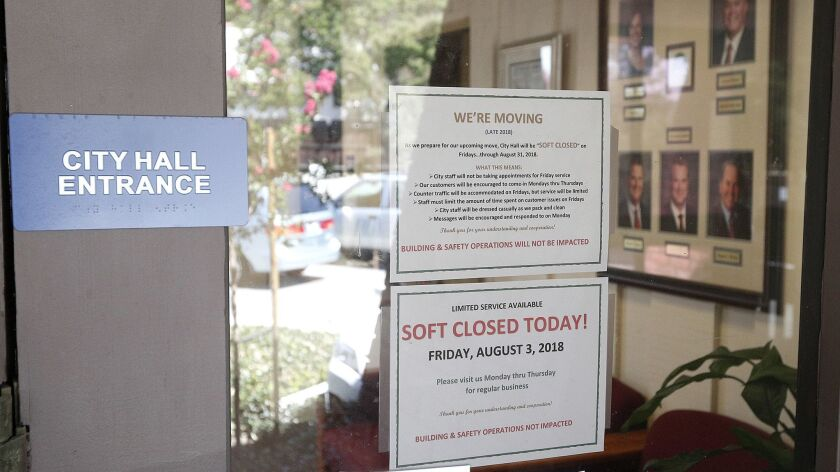 Signs on the front window noting the move, and the soft close where city staff is in the building, b