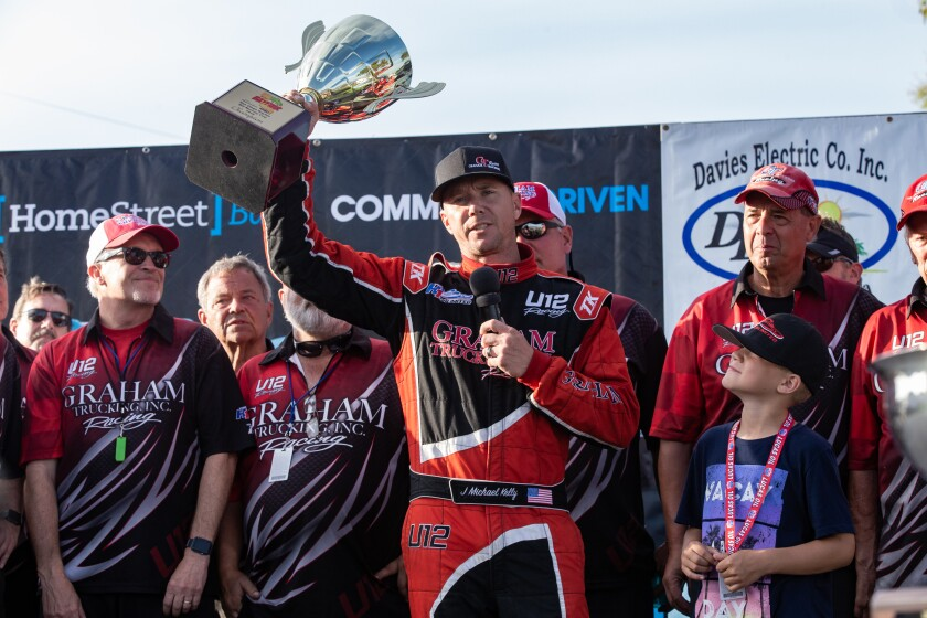 J. Michael Kelly holds up his championship trophy after winning the 2019 H1 Unlimited hydroplane races during San Diego Bayfair on Sunday.