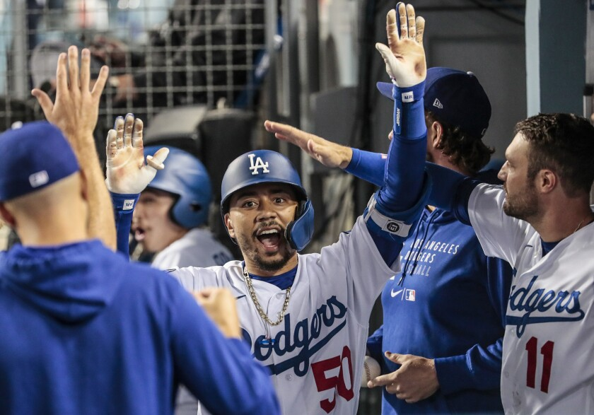 The Dodgers' Mookie Betts celebrates in the dugout after hitting a fourth-inning homer.