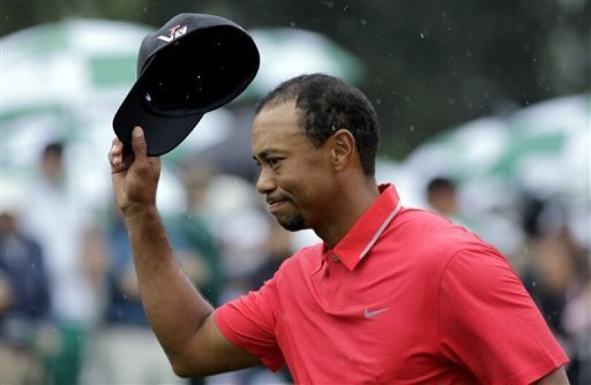 Tiger Woods tips his cap after putting out on the 18th hole during the fourth round of the Masters golf tournament Sunday, April 14, 2013, in Augusta, Ga. (AP Photo/Matt Slocum)