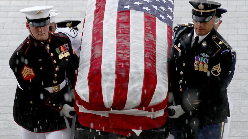 A military honor guard team carries the casket of Sen. John McCain into the U.S. Capitol on Friday.