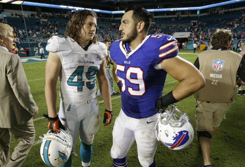 Buffalo Bills linebacker A.J. Tarpley (59) talks with Miami Dolphins linebacker Zach Vigil at the end of an NFL game last season, Tarpley's first year in the league. Citing fears over long-term brain damage from concussions, he recently retired.