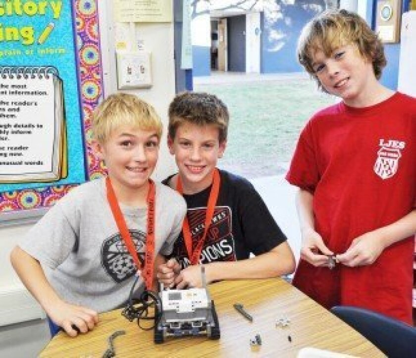 Kristofer Backlund, Ollie Mendel and Keegan Leonard show off their Lego Mindstorms robot. The team recently won the project category of a robotics tournament for their novel solution to extinguish wildfires.