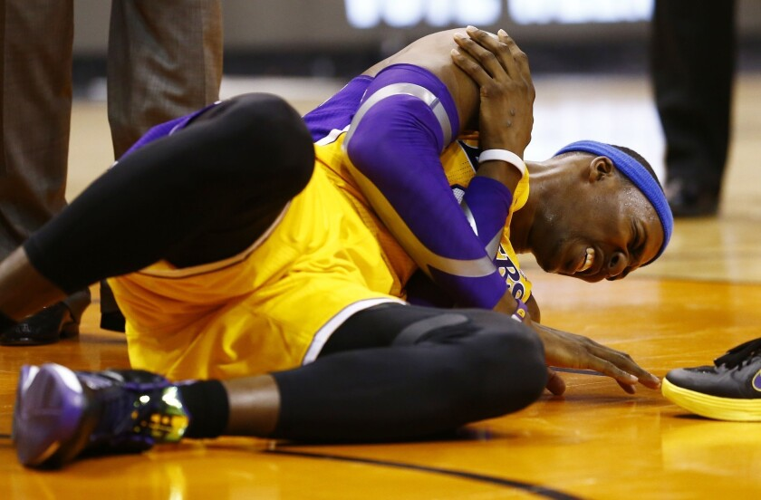 Lakers center Dwight Howard grabs his shoulder in pain during a game against the Phoenix Suns.