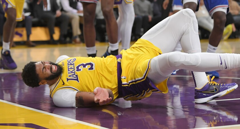 Lakers forward Anthony Davis winces after taking a fall during the third quarter of a game against the New York Knicks on Tuesday at Staples Center.