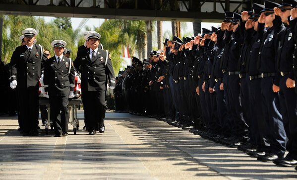 Colleagues stand at attention as the casket of fallen firefighter Kevin Woyjeck, 21, is brought in for a service at the Christ Cathedral campus in Garden Grove on Tuesday. Woyjeck was killed, along with 18 other firefighters, in a blaze in Yarnell, Ariz., on June 30.