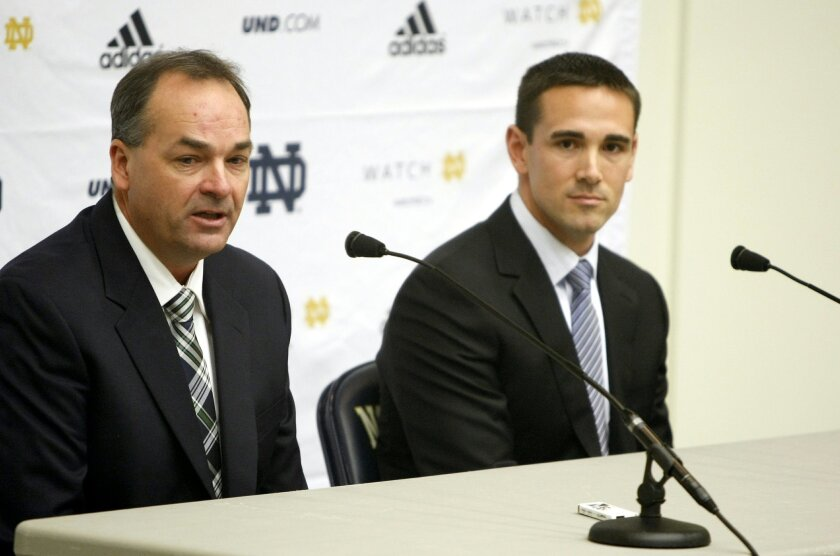 New Notre Dame offensive coordinator Mike Denbrock, left, speaks as new quarterbacks coach Matt LaFleur looks during an NCAA college football news conference, Friday, Jan. 31, 2014, in South Bend, Ind., after head coach Brian Kelly announced the coaching staff appointments. (AP Photo/South Bend Tribune/Greg Swiercz)