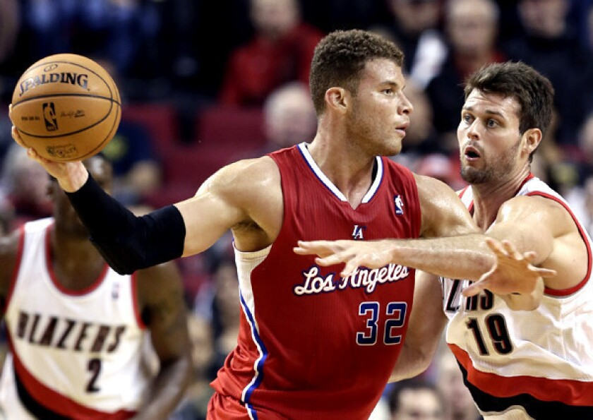 Clippers forward Blake Griffin looks to pass against the defense of Trail Blazers forward Joel Freeland during the second half of a preseason game on Monday.
