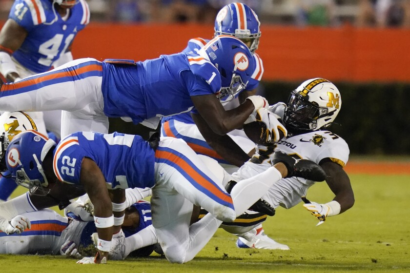 Missouri running back Larry Rountree III, right, is stopped by the Florida defense, including linebacker Brenton Cox Jr. (1) and defensive back Brad Stewart Jr., back, during the first half of an NCAA college football game Saturday, Oct. 31, 2020, in Gainesville, Fla. (AP Photo/John Raoux)
