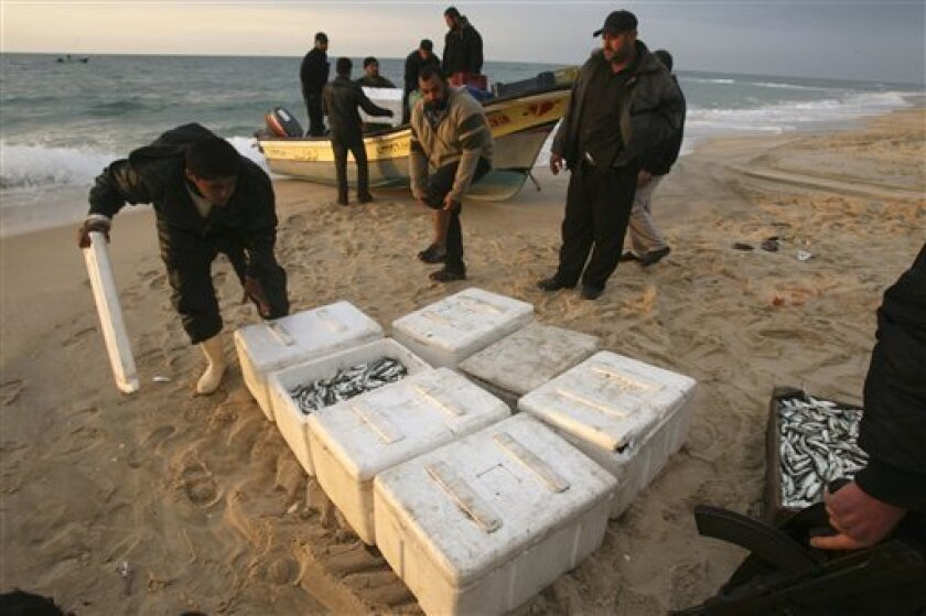 In this photo taken Thursday, Feb. 25, 2010, Palestinian Hamas security officers check boxes of fish, bought from Egyptian fishermen, after they were unloaded from a boat on the beach of the Mediterranean Sea near the Egyptian border in Rafah, southern Gaza Strip. Gaza's desperate fishermen, hemmed in by an Israeli sea blockade, have found new ways of hauling in their daily catch: They're sneaking into Egyptian waters in tiny motorboats and buying fish from their Egyptian counterparts. (AP Photo/Eyad Baba)