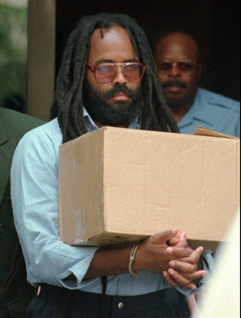FILE - In this July 12, 1995 file photos, convicted police killer and death-row activist Mumia Abu-Jamal leaves Philadelphia's City Hall after a hearing. Mumia Abu-Jamal, a one-time death row inmate now serving a life sentence for the 1981 murder of a Philadelphia police officer spoke to students graduating from a Vermont college on Sunday, Oct. 5, 2014 encouraging them to strive to transform the world.(AP Photo/Chris Gardner, File)