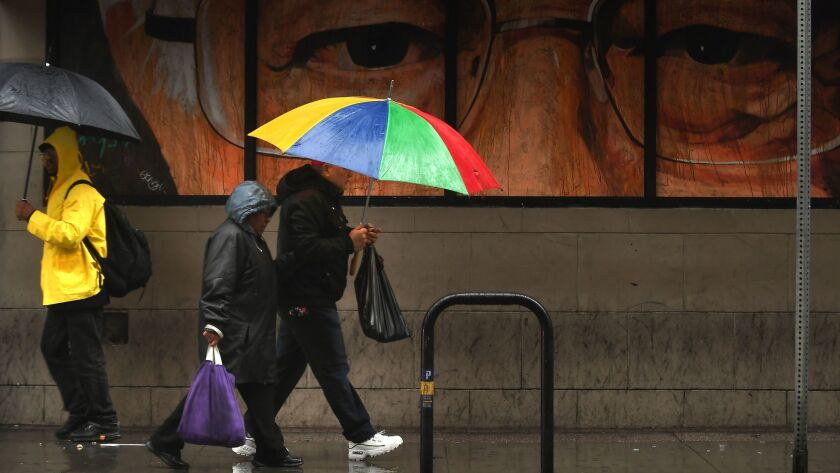 People carrying umbrellas walk past a mural of a close-up of a man wearing glasses on 5th Street.