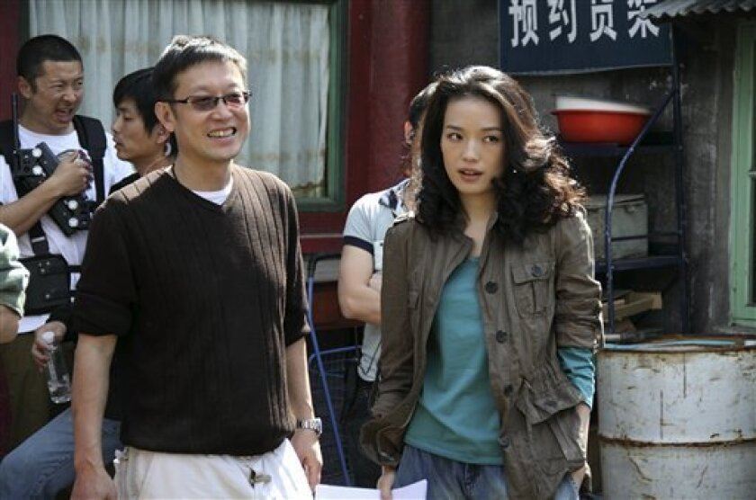 """This undated handout production photo provided by Media Asia Group shows Hong Kong director Andrew Lau, left, instructs Taiwanese actress Shu Qi on a set of his upcoming romance, """"A Beautiful Life."""" Lau, best known for his """"Young and Dangerous"""" series and """"Infernal Affairs"""" trilogy, says his new movie represents a clear departure from the fast-paced, visually dynamic work of his past. (AP Photo/Media Asia Group) NO SALES, NO ARCHIVES"""