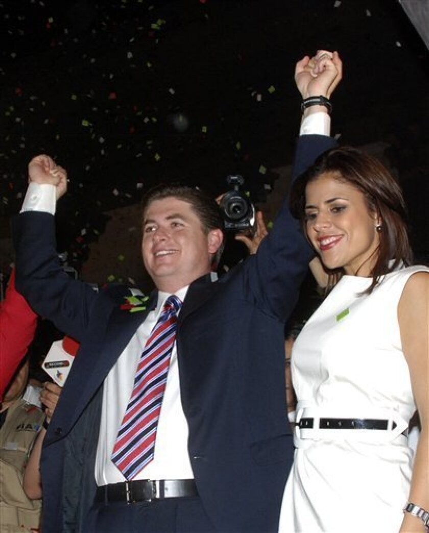 Rodrigo Medina, left, of the Institutional Revolutionary Party, PRI, celebrates alongside his wife, Gretta Salinas, in Monterrey, Sunday, July 5, 2009, after being named the projected winner in gubernatorial elections in Mexico's northern state of Nuevo Leon. The party that ruled Mexico for seven decades appeared to be making a historic comeback in Sunday's midterm congressional elections, scoring big with voters for the first time since it lost the presidency in 2000. (AP Photo)