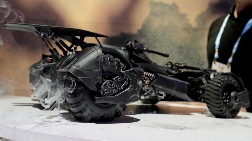 A floor attendant in the Mattel showroom demonstrates features on a new Batmobile, including smoke t