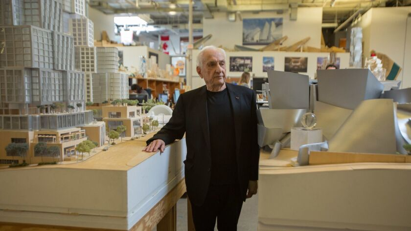 Frank Gehry in his Los Angeles office standing between models of the Grand development and Walt Disney Concert Hall.