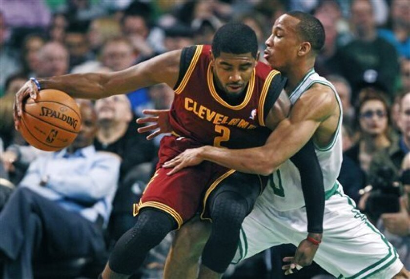 Boston Celtics guard Avery Bradley, right, wraps around Cleveland Cavaliers guard Kyrie Irving (2) on a drive to the basket during the first quarter of an NBA basketball game in Boston, Friday, April 5, 2013. (AP Photo/Charles Krupa)