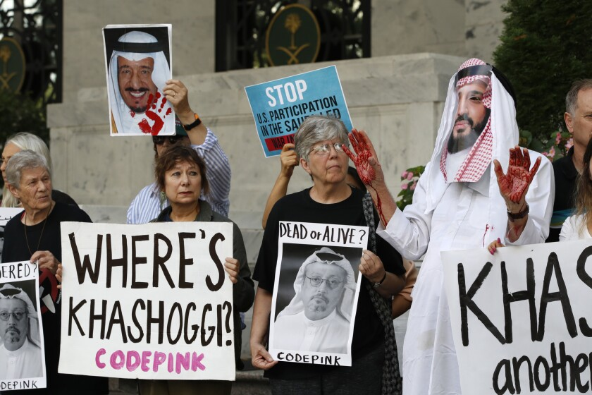 People hold signs at Saudi Arabia embassy in Washington, D.C., during protest earlier this week.
