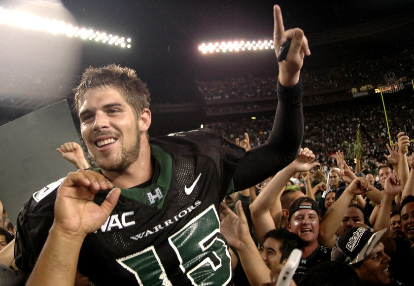 Hawaii quarterback Colt Brennan holds a finger up as he celebrates with the crowd after an NCAA college football game