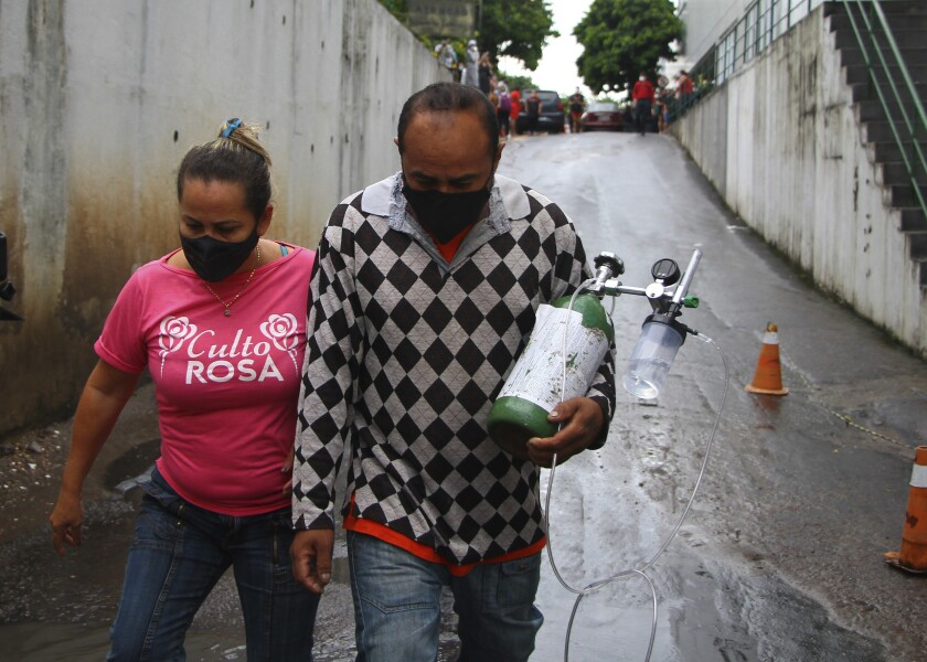 A man carries an oxygen tank that he bought for his mother-in-law, who is hospitalized with COVID-19, in Manaus, Brazil.